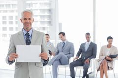 Smiling businessman holding a blank notice. With people waiting behind royalty free stock photos