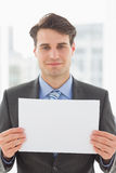 Smiling businessman holding blank page. In the office Stock Photos