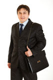 Smiling businessman holding briefcase on shoulder Stock Image