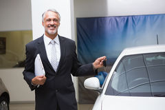 Smiling businessman holding car key and folder Stock Images