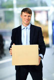 Smiling businessman holding a cardboard box Stock Images