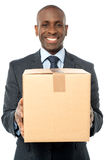 Smiling businessman holding carton box Stock Image