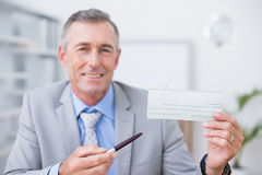 Smiling businessman holding cheque Royalty Free Stock Image
