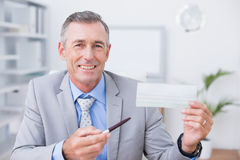 Smiling businessman holding cheque Stock Images