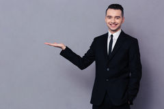 Smiling businessman holding copyspace on the palm Royalty Free Stock Image