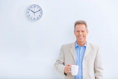Smiling businessman holding a cup of coffee Royalty Free Stock Photo