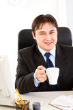 Smiling businessman holding cup of tea in hand Royalty Free Stock Photos