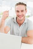 Smiling businessman holding cup and using laptop Stock Images