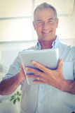 Smiling businessman holding digital tablet at office Stock Images