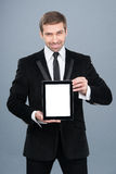 Smiling businessman holding digital tablet pc with blank screen. Royalty Free Stock Images