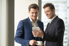 Smiling businessman holding digital tablet showing something fun. Smiling happy businessman holding digital tablet showing something funny interesting to Royalty Free Stock Photo