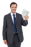 Smiling businessman holding dollar bills Stock Images
