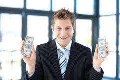 Smiling businessman holding dollars Stock Photo