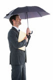 Smiling businessman holding a file under umbrella Royalty Free Stock Images
