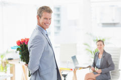 Smiling businessman holding flowers behind his back Stock Image