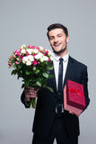 Smiling businessman holding flowers and gift box Stock Photos