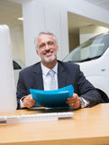 Smiling businessman holding a folder at his desk Royalty Free Stock Photography