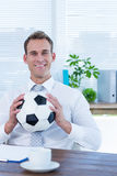 Smiling businessman holding a football Royalty Free Stock Photo