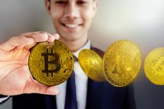 Smiling Businessman holding Golden Bitcoin Money. Happy to Earn. And Pay a Digital Cryptocurrency Royalty Free Stock Photos