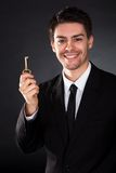 Smiling businessman holding a golden key Royalty Free Stock Photo