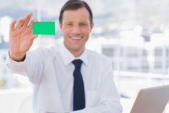 Smiling businessman holding a green business card Royalty Free Stock Photos
