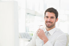 Smiling businessman holding his glasses stock photo