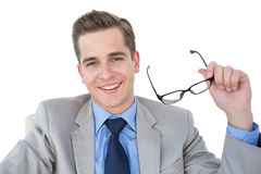 Smiling businessman holding his glasses Stock Photography