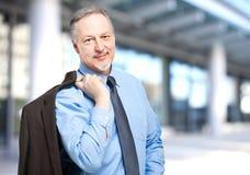 Smiling businessman holding his jacket on the shoulder Stock Image