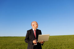 Smiling Businessman Holding Laptop On Field Stock Photos