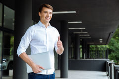 Smiling businessman holding laptop and showing thumbs up. Smiling successful young businessman holding laptop and showing thumbs up Royalty Free Stock Photo