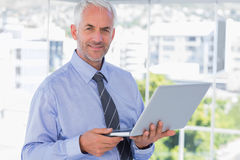 Smiling businessman holding laptop. Standing in office Stock Photos