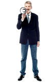Smiling businessman holding a megaphone. Full length image of businessman using a loudhailer Royalty Free Stock Photo