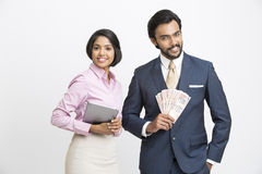 Smiling businessman holding money with his colleague. Happy smiling businessman holding money with his colleague on white background Stock Photography