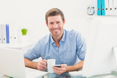 Smiling businessman holding mug and phone Royalty Free Stock Images