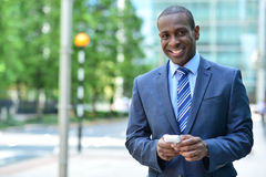 Smiling businessman holding smartphone Royalty Free Stock Image