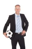 Smiling businessman holding soccer ball Royalty Free Stock Photo