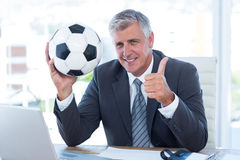 Smiling businessman holding soccer ball with thumbs up Royalty Free Stock Images