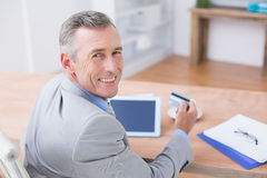 Smiling businessman holding tablet and credit card Royalty Free Stock Photo