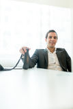 Smiling Businessman Holding Telephone on his Desk Stock Photography