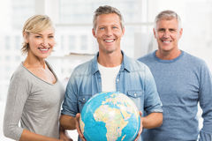 Smiling businessman holding terrestrial globe Stock Photo