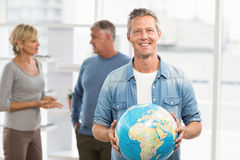 Smiling businessman holding terrestrial globe Stock Photography