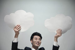 Smiling businessman holding two paper clouds, studio shot Stock Image
