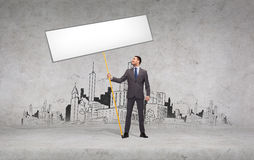 Smiling businessman holding white blank board Royalty Free Stock Images