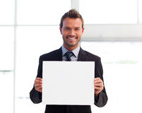Smiling businessman holding a white card Royalty Free Stock Images
