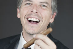 Smiling Businessman Holds Cigar Royalty Free Stock Photography