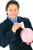 Smiling Businessman Insert Money To Piggy Bank. Young handsome businessman inserting money into piggy bank royalty free stock photo