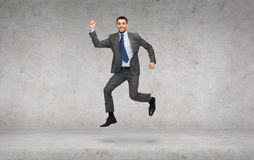 Smiling businessman jumping. Business and education concept - smiling businessman jumping Stock Photography