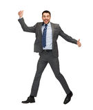 Smiling businessman jumping and showing thumbs up Royalty Free Stock Image