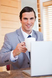 Smiling businessman with laptop and coffee Stock Images