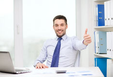 Smiling businessman with laptop and documents Stock Image